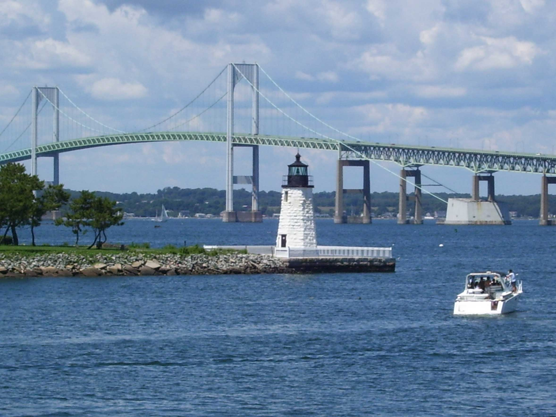 Photograph of the Newport harbor with a lighthouse and Newport bridge in the background
