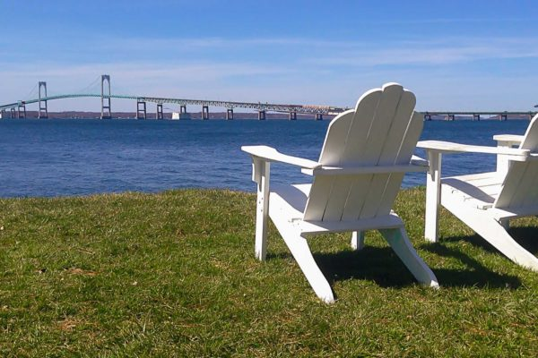 Photograph of two adirondack chairs overlooking the water and Newport bridge