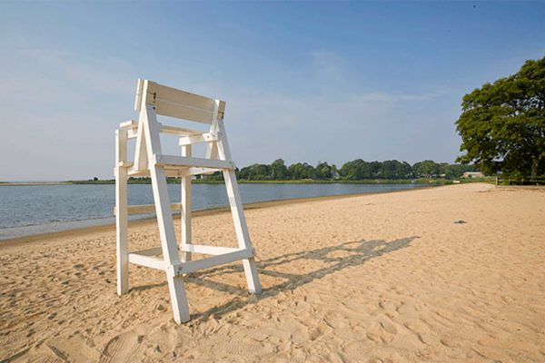 Photograph of a tall, white wood chair overlooking the water on a beach in Warwick
